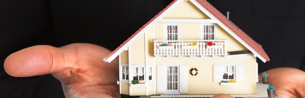 African Businessman Holding House Model